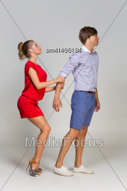 Young Man Leaving His Girlfriend Over Grey Background Stock Photo