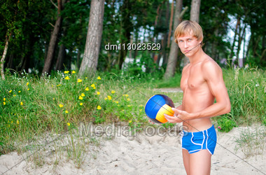 Young Man Posing With The Ball On The Beach Stock Photo