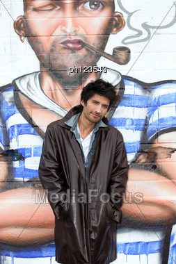 Young Man Posing In Front Of Graffiti Wall Stock Photo