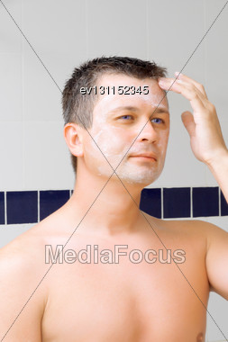 Young Man Puts On Face Cream Mask In Bathroom Stock Photo