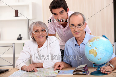 Young Man And Senior Couple Seeking A Route On A Map Stock Photo