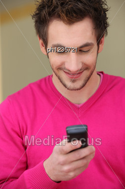 Young Man Smiling At His Phone Stock Photo