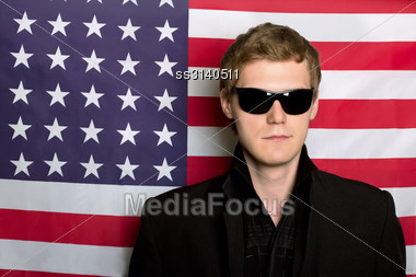 Young Man In Sunglasses On A Background Of The American Flag Stock Photo