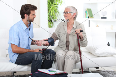 Young Man Taking The Blood Pressure Of An Older Lady Stock Photo