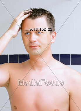 Young Man Uses A Lotion After Shaving In Bathroom Stock Photo
