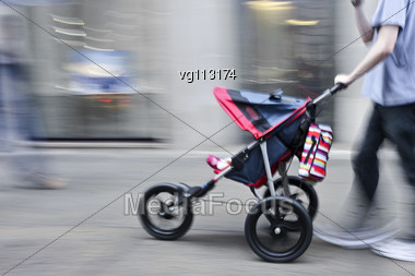 Young Parent With Stroller Rushing On The Street In Intentional Motion Blur Stock Photo