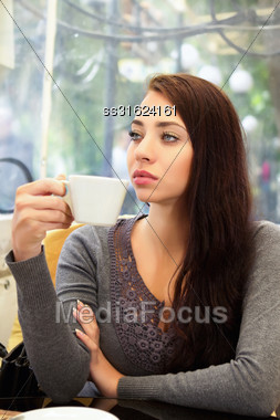 Young Pensive Woman Drinking In A Cozy Cafe Stock Photo