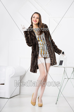 Young Playful Brunette Posing In Short Dress And Fur Coat Stock Photo