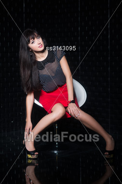 Young Playful Woman Posing On The Chair Indoors Stock Photo