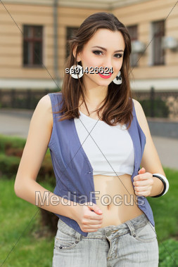 Young Playful Woman Wearing Short Top And Vest Posing Outdoors Stock Photo