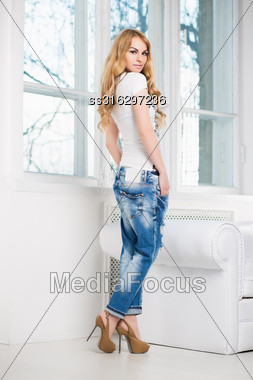 Young Pretty Blond Woman Posing In Blue Jeans And White T-shirt Near The Window Stock Photo