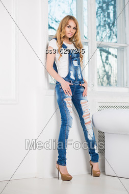 Young Pretty Woman Posing In Ragged Denim Overalls Near The Window Stock Photo