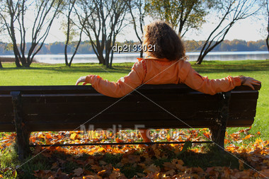 Young red hair woman sitting on the bench at the river Stock Photo
