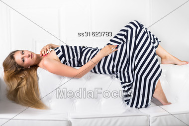 Young Sexy Blond Woman Lying On The White Sofa Stock Photo