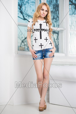 Young Sexy Blond Woman Posing In Denim Shorts And White T- Shirt Near The Window Stock Photo