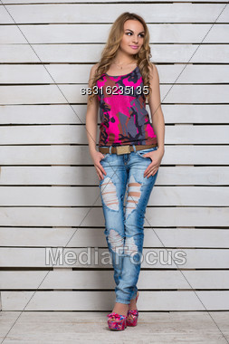 Young Sexy Blond Woman Posing In Ripped Jeans And Top Near White Wooden Wall Stock Photo