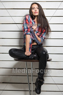 Young Sexy Brunette Posing In Checked Shirt And Leather Pants Stock Photo