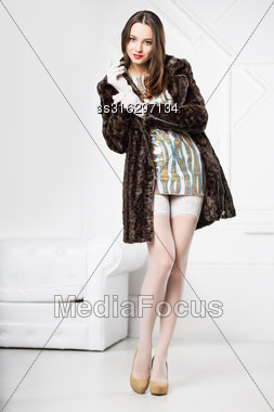Young Sexy Brunette Posing In Frank Dress, White Stockings And Fur Coat Stock Photo