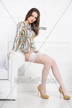 Young Sexy Brunette Wearing Frank Dress And White Stockings Posing Near Sofa Stock Photo