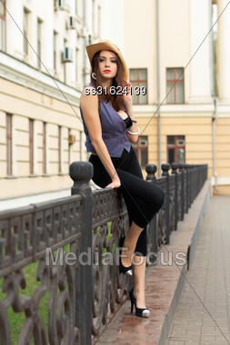 Young Sexy Woman In Black Leggings Sitting On The Metallic Fence Stock Photo