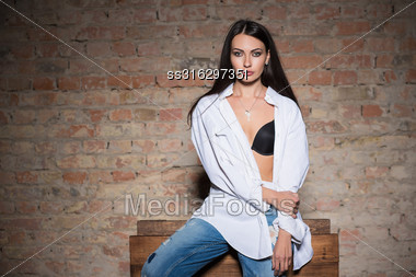Young Sexy Woman Posing In Black Bra, White Shirt And Blue Jeans Stock Photo