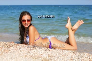 Young Sexy Woman In Swimsuit Posing On The Beach Stock Photo