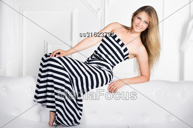 Young Sexy Woman Wearing Long Dress Posing On The White Sofa Stock Photo