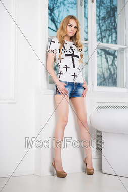 Young Slim Blond Woman Posing In Denim Shorts And White T- Shirt Near The Window Stock Photo