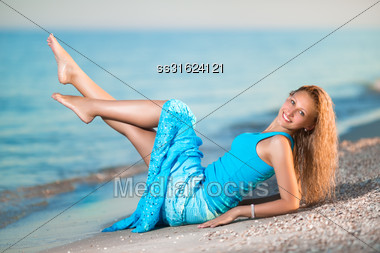 Young Smiling Blonde Showing Her Legs On The Beach Stock Photo