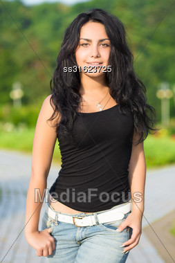 Young Smiling Brunette In Blue Jeans And Black T-shirt Posing In The Park Stock Photo