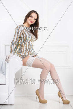Young Smiling Brunette Wearing Frank Dress And White Stockings Posing Near Sofa Stock Photo