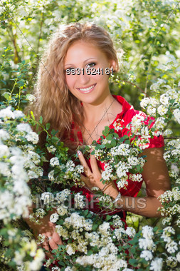 Young Smiling Lady Posing Near The Flowering Bush Stock Photo