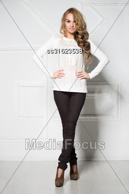 Young Smiling Woman In Black Pants And White Blouse Posing Near The Wall Stock Photo
