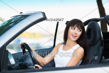 Young Smiling Woman Posing In Grey Car Stock Photo