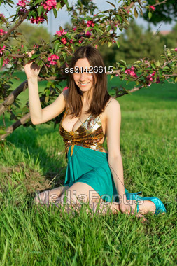 Young Smiling Woman Sitting On The Grass Near A Flowering Tree Stock Photo