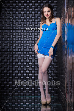 Young Smiling Woman Wearing Blue Dress Posing In The Black Room Stock Photo