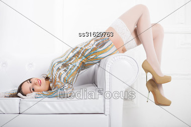 Young Smiling Woman Wearing Frank Dress And White Stockings Posing On The Sofa Stock Photo
