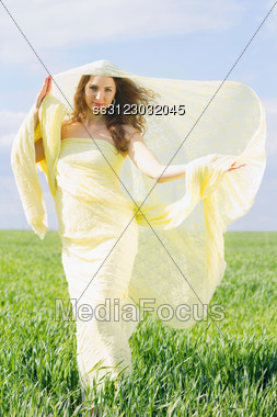 Young Smiling Woman Wrapped In Yellow Cloth Stock Photo