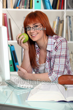 Young Student Holding Apple In Library Stock Photo