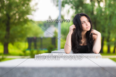 Young Thoughtful Brunette Posing Near The Stone Fence Stock Photo