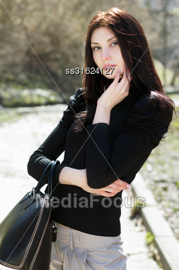 Young Thoughtful Lady With Black Bag Posing Outdoors Stock Photo