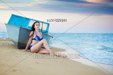 Young Thoughtful Woman Posing Near The Boat Stock Photo