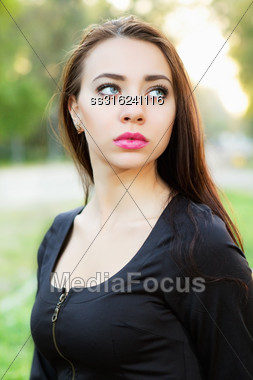 Young Thoughtful Woman Wearing Black Dress Posing Outdoor Stock Photo