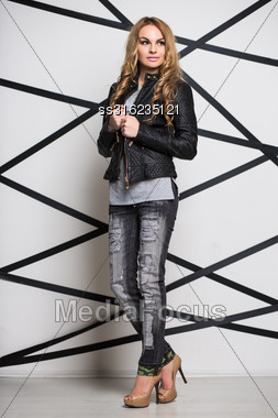 Young Thoughtful Woman Wearing Leather Jacket And Gray Jeans Stock Photo