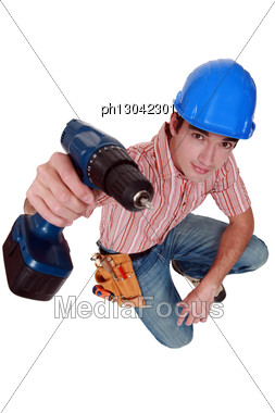 Young Tradesman Looking Fixedly At Camera With Electric Drill Stock Photo