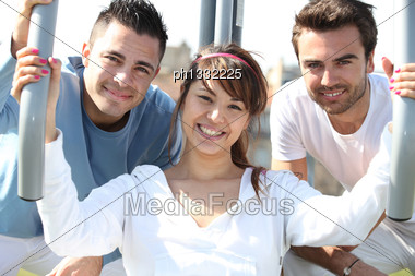 Young Trio Using An Outdoor Gym Stock Photo