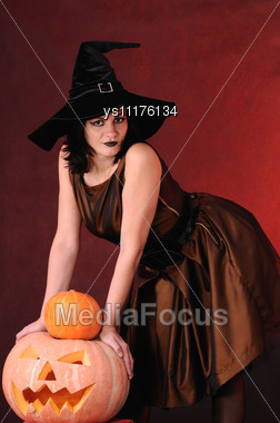 Young Witch With A Pumpkin Stock Photo