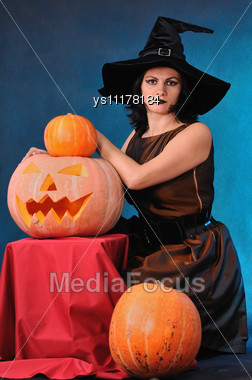 Young Witch With A Pumpkin On A Blue Background Stock Photo
