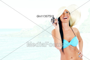 Young Woman In Bikini And Straw Hat On A Seashore Background Stock Photo