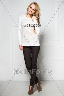 Young Woman In Black Pants And White Blouse Posing Near The Wall Stock Photo